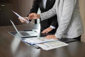 zakenvrouw en zakenman die documenten analyseren foto