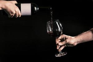 handen die wijn in glas gieten foto