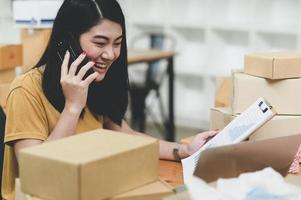 vrouw die producten online verkoopt, telefoneert en de voorraad controleert, foto