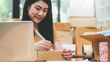 vrouw schrijft een adres op een pakketdoos voor levering aan een klant. foto