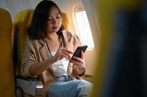 jonge vrouwen gebruiken smartphones tijdens vliegtuigreizen. foto