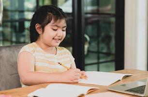 een Aziatisch kindmeisje in een goed humeur studeert thuis. foto
