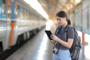 een buitenlandse vrouwelijke reiziger draagt een rugzak met behulp van een tablet terwijl ze op een trein wacht. foto