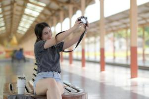een vrouwelijke tienertoerist neemt een selfie terwijl ze wacht op een reis. foto