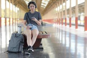 een jonge vrouwelijke reiziger luistert naar muziek met een koptelefoon terwijl ze wacht op haar reis op het perron. foto