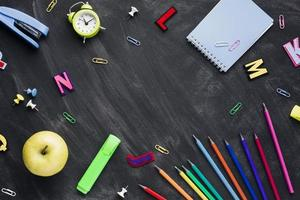 schoolbenodigdheden met appel en wekker op verspreid schoolbord foto