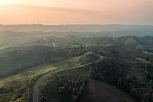 luchtfoto van gebogen snelweg op groene heuvel en windturbine op piek bij zonsondergang op het platteland foto