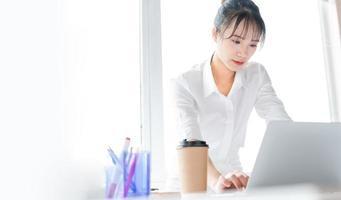 portret van een jonge zakenvrouw die staat en samenwerkt met een laptop? foto