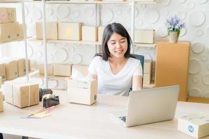 Aziatische vrouwelijke bedrijfseigenaar die thuis werkt met een verpakkingsdoos op de werkplek foto