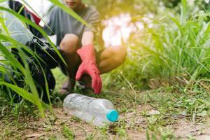 jongen man hand pick-up plastic fles in bos. milieu concept. foto