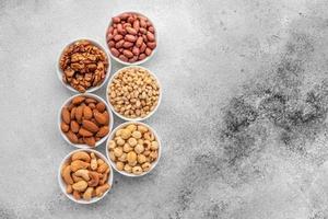 assortiment noten in witte schotels op een betonnen ondergrond foto