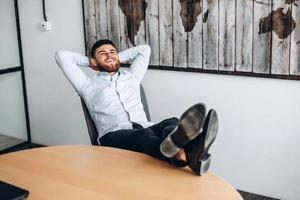 een aantrekkelijke man met een baard legt zijn handen achter zijn hoofd, zet zijn voeten op tafel en rust. foto