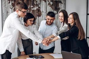 jonge zakenmensen die hun handen in elkaar slaan. stapel handen. eenheid en teamwork concept. foto