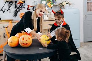 moeder en kinderen tekenen op pompoen, spelen en hebben grappige tijd thuis. -halloween-concept foto