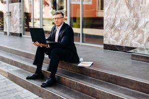 portret van senior man in pak zitten en houden van een opengeklapte laptop buiten. - afbeelding foto