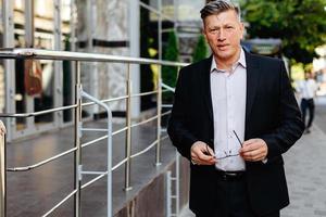 bedrijfs- en mensenconcept - senior zakenman die een bril in zijn hand houdt in de stad foto