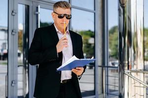 portret van senior zakenman die een document vasthoudt en denkt. - afbeelding foto