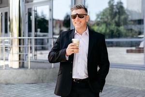 portret van senior zakenman staande op de stoep met een kopje koffie en glimlachen. - afbeelding foto