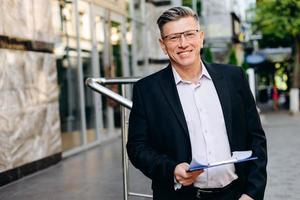 lachende senior zakenman in glazen die een document vasthoudt en naar de camera kijkt - afbeelding foto