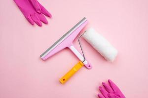 raamreinigingsborstel en -rol voor reparatie en rubberen handschoenen op een roze achtergrond foto
