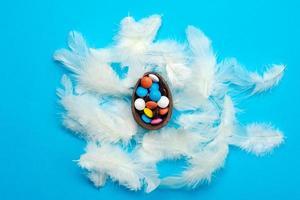 witte veren liggen op de blauwe achtergrond van Pasen. veelkleurige snoepjes in het chocolade-ei foto
