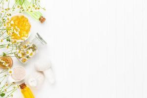 spa stilleven met zelfgemaakte cosmetische kamille, kruidenolie, zeep, zeezout. foto