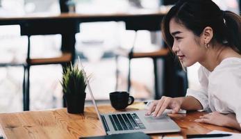 zakenvrouw met behulp van laptop werken met rekenmachine voor financiële. uitknippad foto