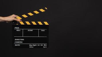 hand houdt zwart met gele kleur klapbord of film leisteen gebruik in videoproductie en filmindustrie op zwarte achtergrond. foto