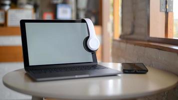 mockup laptop leeg scherm en hoofdtelefoon op scherm, laptop op een tafel in een café geplaatst. foto