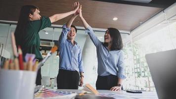 grafisch ontwerperteam hield hun handen vast om hun vreugde uit te drukken na het voltooien van de projectklantdeal. foto