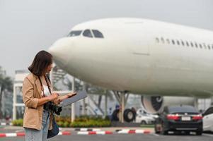 vrouwelijke reizigers vinden toeristische informatie op tablet, vliegtuigachtergrond. foto