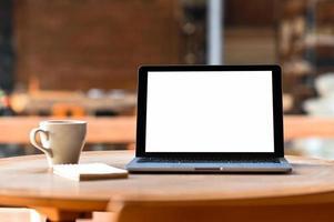 mockup leeg scherm laptop met koffie en notebook op tafel, vanaf de voorkant genomen. foto