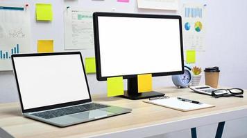 leeg scherm mockup computer en laptop met kantoorapparatuur op het bureau op kantoor. foto