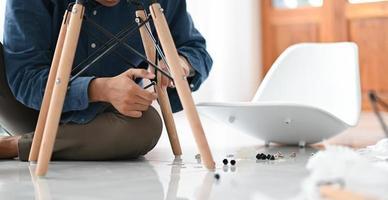 een jonge man die een stoel in huis monteert, repareert de stoel voor hergebruik. foto