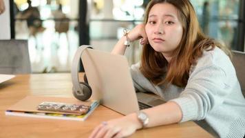 jong Aziatisch meisje dat naar de camera kijkt en een verward gezicht maakt, leun achterover en ontspan terwijl ze thuis online studeert. foto