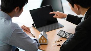 bankpersoneel met laptop die woningkrediet, huismodel en rekenmachine op tafel aanbeveelt. foto