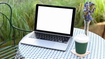 mockup laptop wit leeg scherm met afhaalkoffiemok op tafel. foto