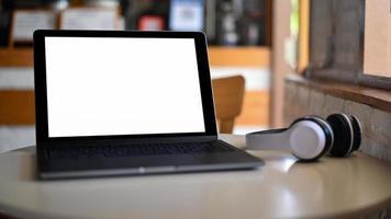 mockup laptop leeg scherm en hoofdtelefoon op geplaatst op een tafel in een café. foto