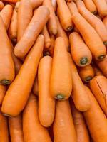 biologische wortel. textuurachtergrond van verse grote oranje wortelen, wortelen zijn goed voor de gezondheid, gezonde rijpe wortel voor het bereiden van maaltijd foto