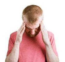 zieke, bebaarde man die zijn hoofd vasthoudt foto