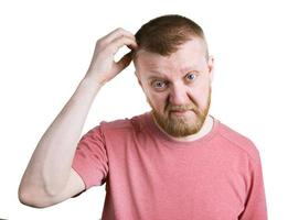 bebaarde man krabt zijn hoofdhaar foto