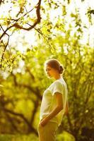 gelukkig meisje dat in de zomertuin staat foto