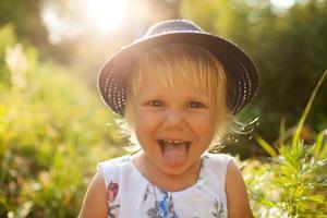 vrolijk blond meisje met een blauwe hoed toont tong foto