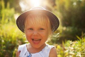 schattig klein vrolijk blond meisje foto