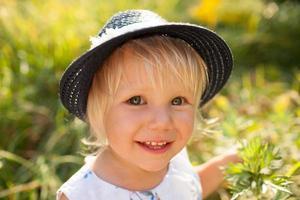 klein blond meisje met blauwe hoed foto