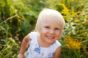 klein meisje in zomerjurk kijkt in een camera foto