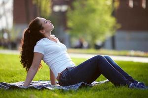 gelukkige vrouw zit op het gras foto