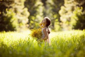 klein meisje staat met een boeket gele bloemen foto