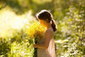 klein meisje staat met een boeket foto