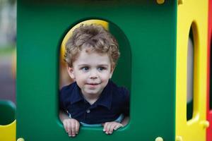 kleine jongen verstopt in een speelhuisje foto